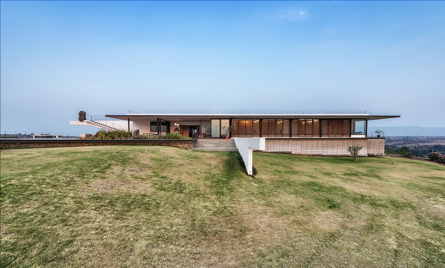 Exterior, Stucco Siding Material, Flat RoofLine, and House Building Type The Soaring Rock was completed January 2018 in Maharashtra, India.  Photo 1 of 14 in A Modern Home in India Evokes Emotion With a Giant 4-Ton Rock