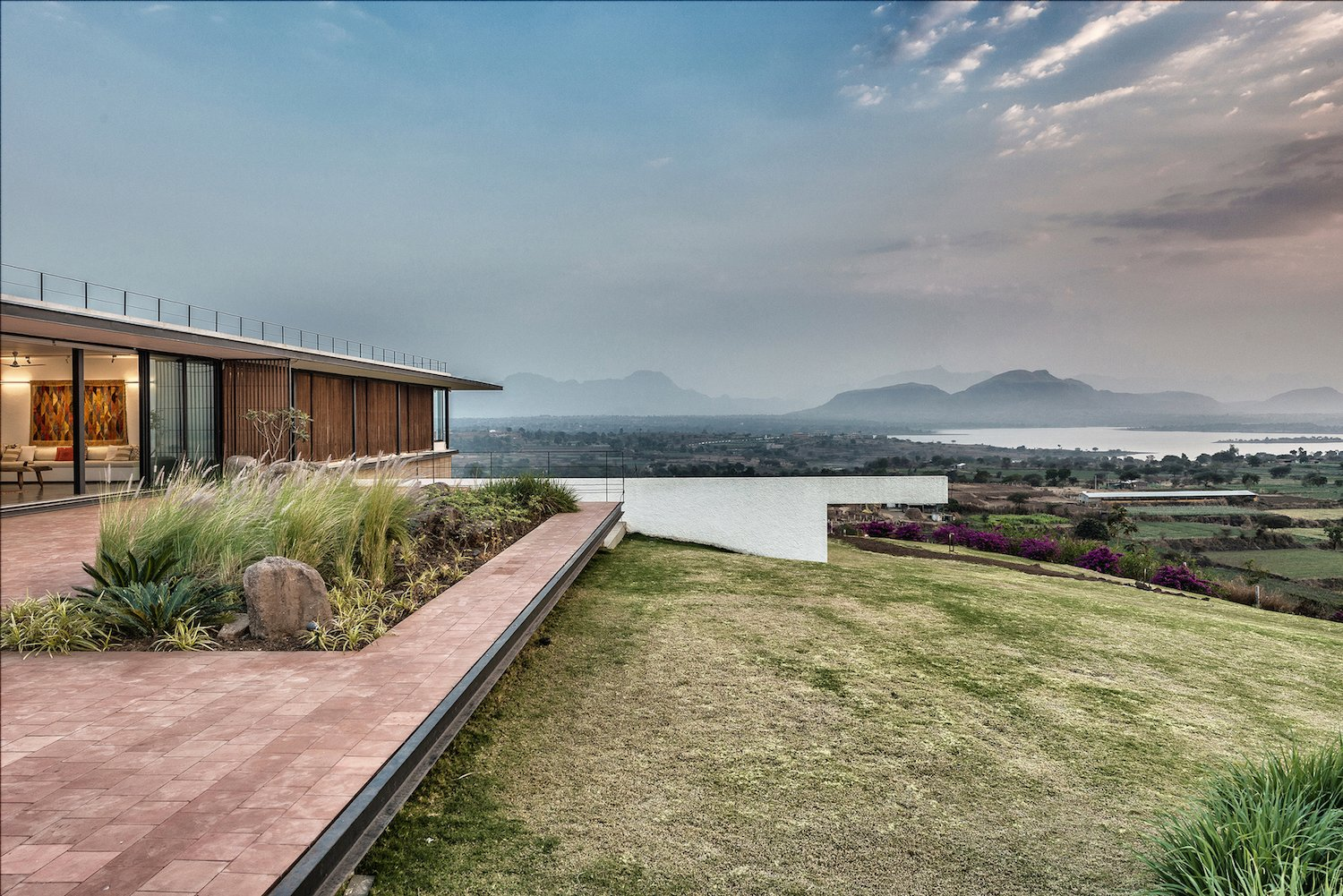 Outdoor, Slope, Large Patio, Porch, Deck, Grass, and Stone Patio, Porch, Deck The home is set on the top of a hill for prime views.  Photo 4 of 14 in A Modern Home in India Evokes Emotion With a Giant 4-Ton Rock