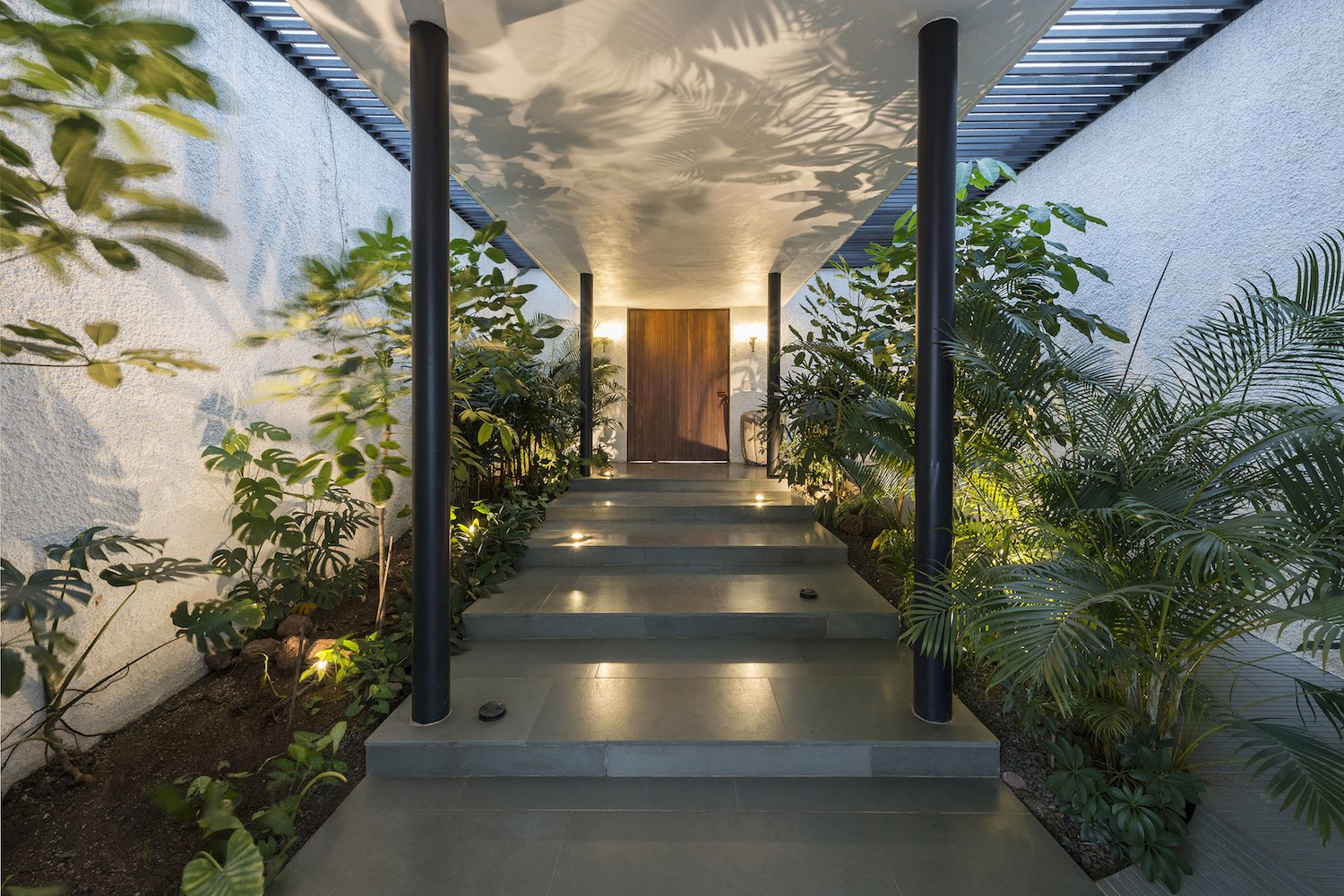 Exterior, Flat RoofLine, House Building Type, and Stucco Siding Material Uplights accent the lush landscaping flanking the entrance.   Photo 11 of 14 in A Modern Home in India Evokes Emotion With a Giant 4-Ton Rock