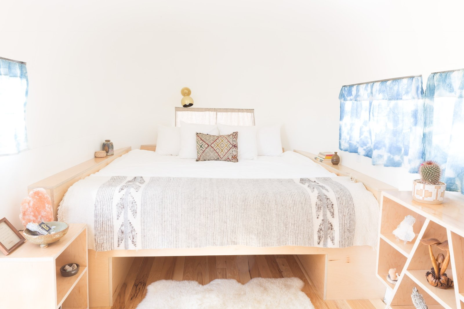 Bedroom, Wall, Night Stands, Bed, Rug, and Light Hardwood Plush Casper Beds, white linens, and cozy touches can be found in all the Airstreams.  Best Bedroom Wall Rug Light Hardwood Bed Photos from Joshua Tree Is Now Home to a Chic Airstream Oasis—Featuring 4 Trailers Available to Rent