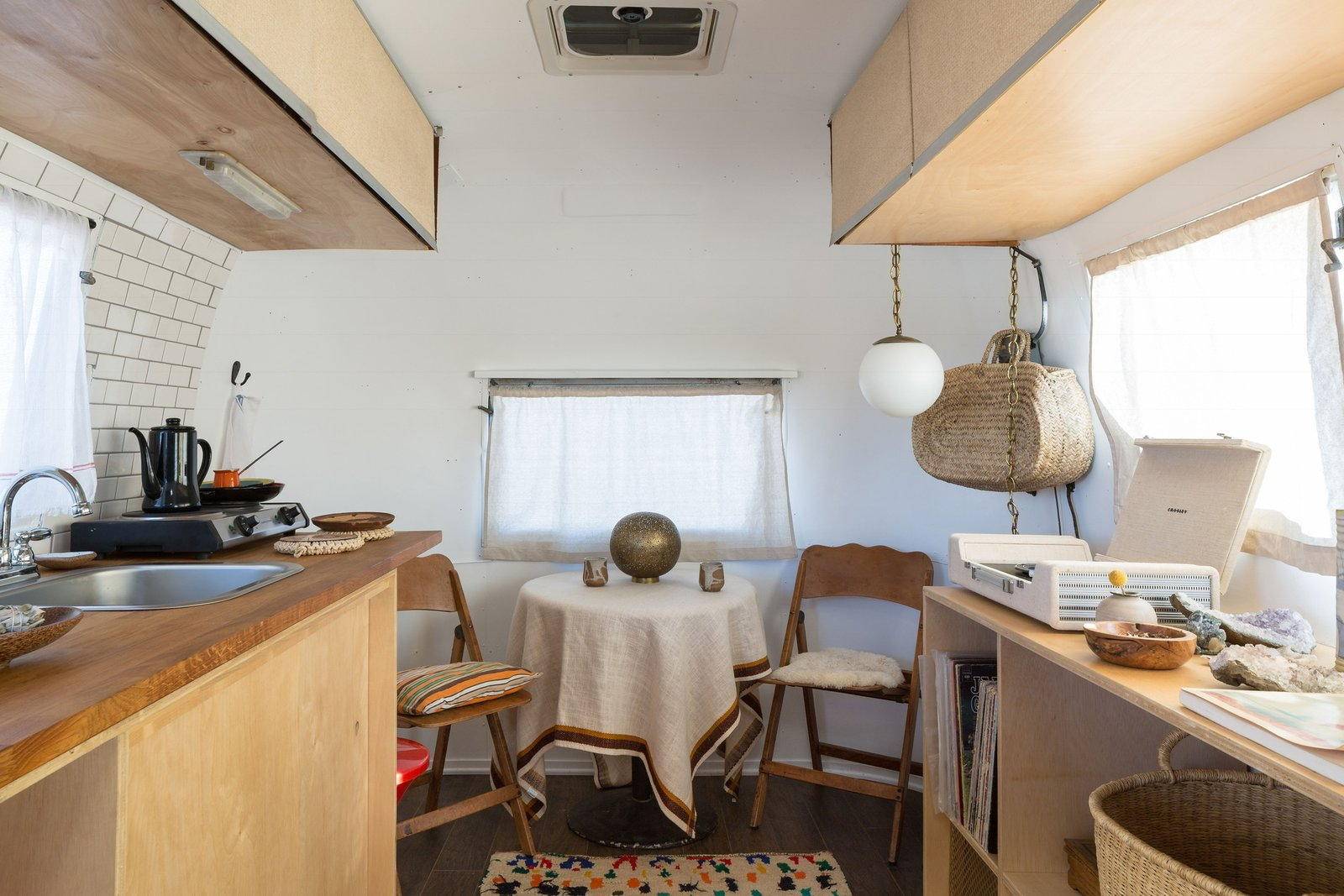 Dining Room, Table, Chair, Pendant Lighting, Rug Floor, and Medium Hardwood Floor The Merchant on the Road Airstream interior was curated by the mother/daughter duo of Merchant Modern.  Photo 9 of 16 in Joshua Tree Is Now Home to a Chic Airstream Oasis—Featuring 4 Trailers Available to Rent