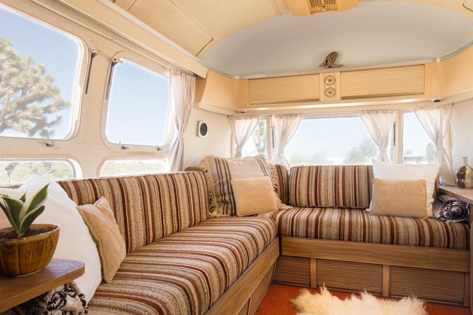 Living Room, Sofa, and Rug Floor Many of the furnishings were handmade and decorations thrifted.   Photo 16 of 16 in Joshua Tree Is Now Home to a Chic Airstream Oasis—Featuring 4 Trailers Available to Rent