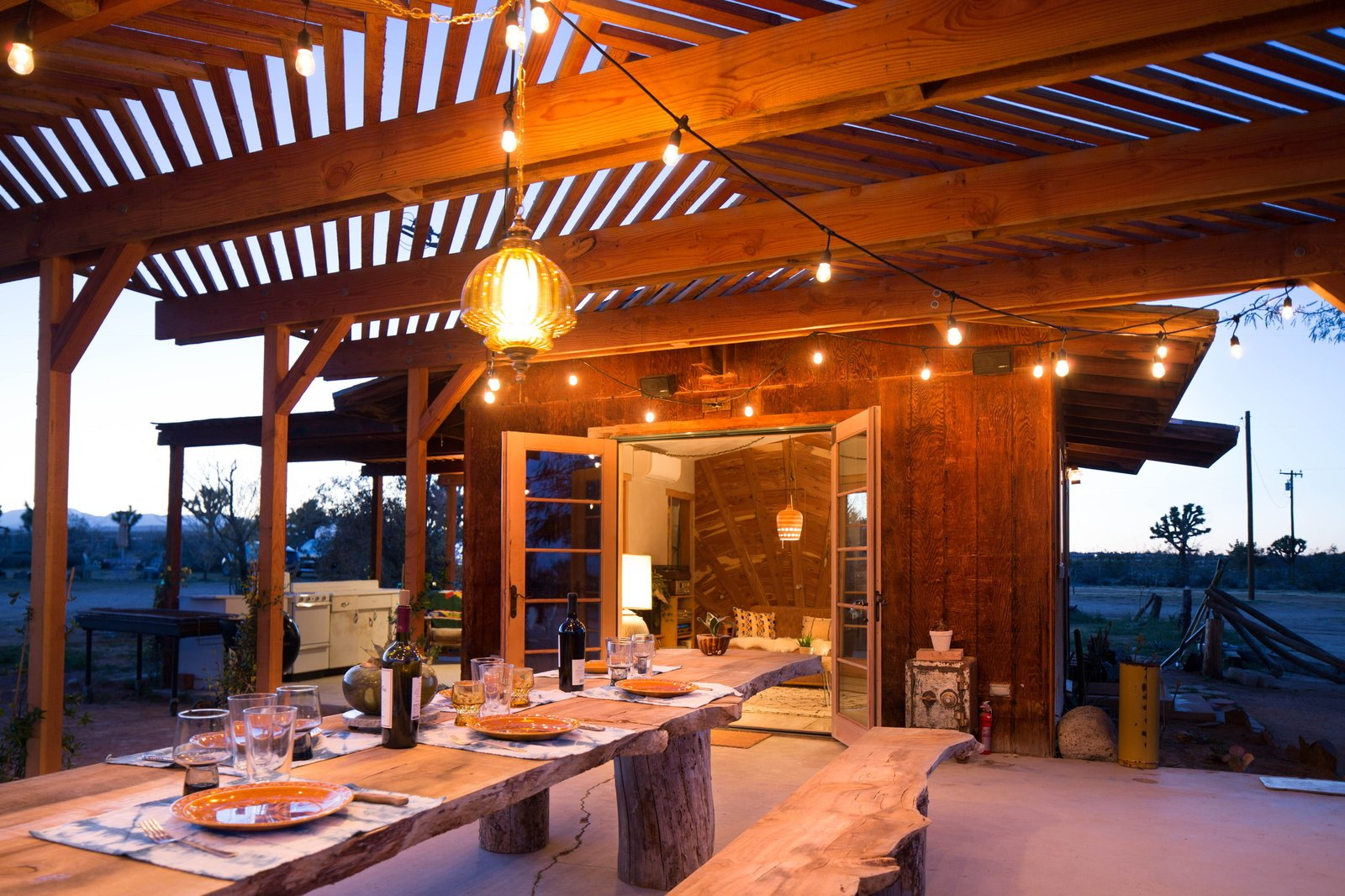 Dining Room, Table, Bench, and Pendant Lighting The Clubhouse also includes an outdoor shower powered by a solar hot-water tank, which was designed by their neighbor Dusty Devine.    Photo 7 of 16 in Joshua Tree Is Now Home to a Chic Airstream Oasis—Featuring 4 Trailers Available to Rent