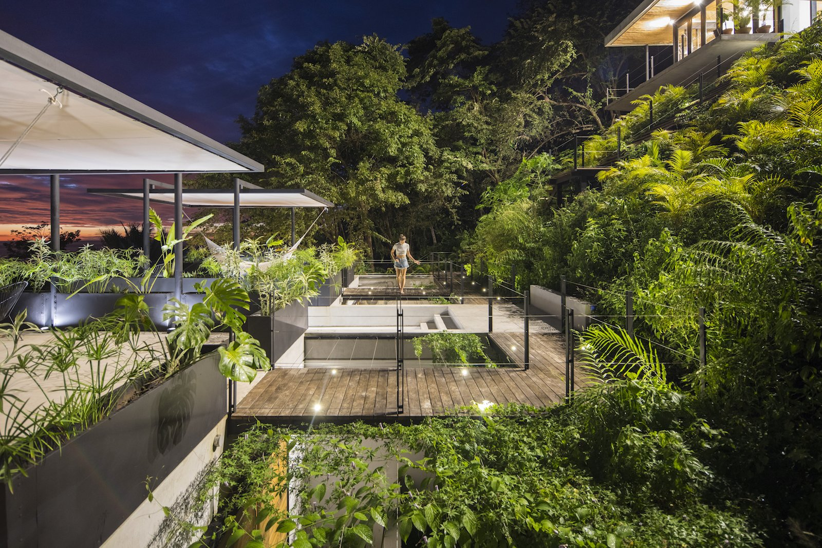 Outdoor, Shrubs, Slope, Small Patio, Porch, Deck, Trees, Wire Fences, Wall, Wood Patio, Porch, Deck, and Grass Locally sourced materials are used throughout the project.  Photo 8 of 11 in Revive Your Mind at This Adults–Only Boutique Hotel in Costa Rica