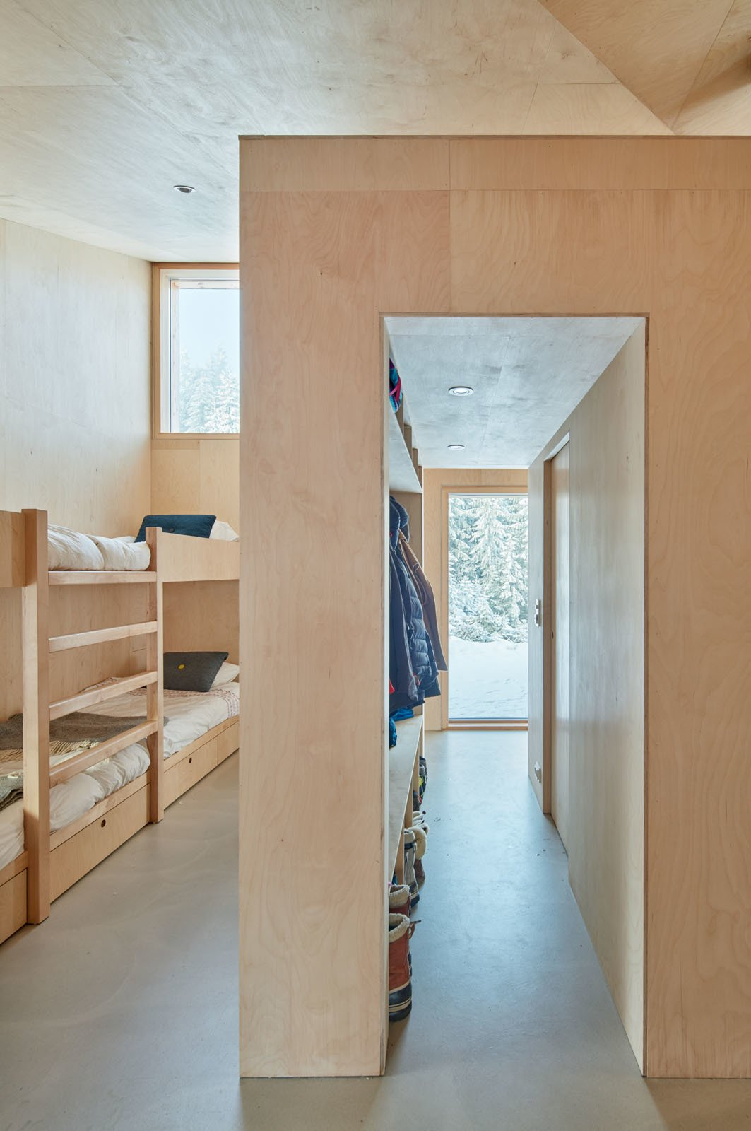 Bedroom, Recessed Lighting, Concrete Floor, and Bunks Each bedroom has two access doors, which close completely flush for a clean appearance.  Photos from A Pinwheel-Shaped Cabin in Norway Is a Fresh Take on the Traditional Hytte