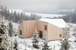 Planning regulations required a gable roof, which the architects split into four shed roofs carefully designed to respond to heavy snow shed and meet spatial and aesthetic wishes.