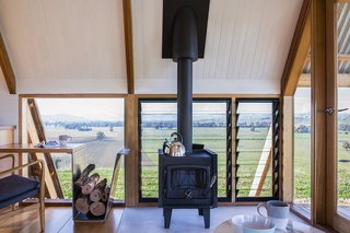 A freestanding Nectre wood-burning stove provides extra warmth in winter, while operable louvers let in cooling breezes in summer.
