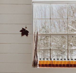 Bottled maple syrup line the windowsill in the couple's new pottery studio.