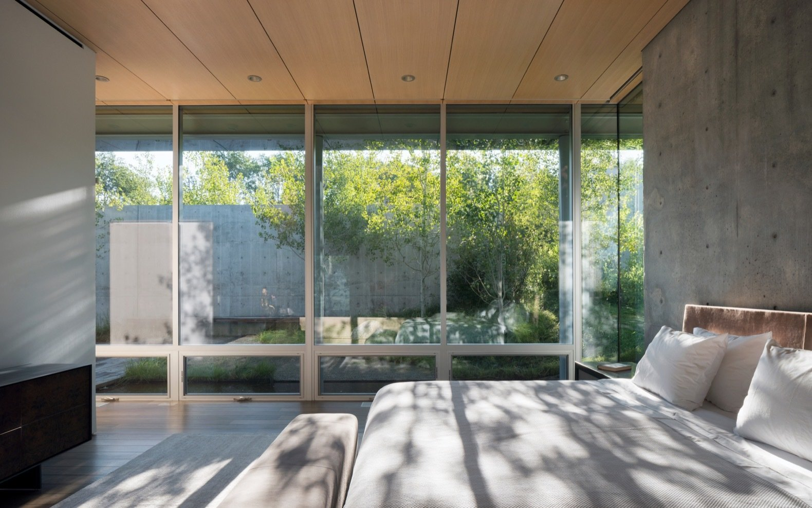 Bedroom, Light Hardwood Floor, Recessed Lighting, and Bed The subdued interior palette comprises of exposed smooth-formed concrete, painted drywall, and rough-sawn cedar.    Photo 14 of 17 in A Modern House Accentuates a Sensational Wyoming Landscape