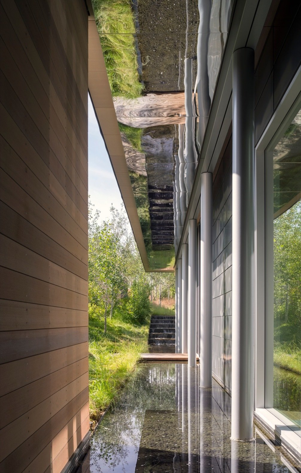 Outdoor, Trees, Small Pools, Tubs, Shower, and Grass Located between the courtyard and the home, the shallow linear pool on the north-south axis is reflected by mirrored-finish panels.    Photo 7 of 17 in A Modern House Accentuates a Sensational Wyoming Landscape