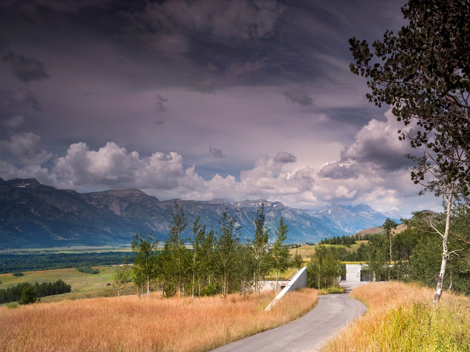 Outdoor, Grass, Trees, and Slope Set at an elevation of 6,700 feet, the home overlooks extraordinary views of the Snake River Valley and the Teton Mountain Range.    Photo 2 of 17 in A Modern House Accentuates a Sensational Wyoming Landscape