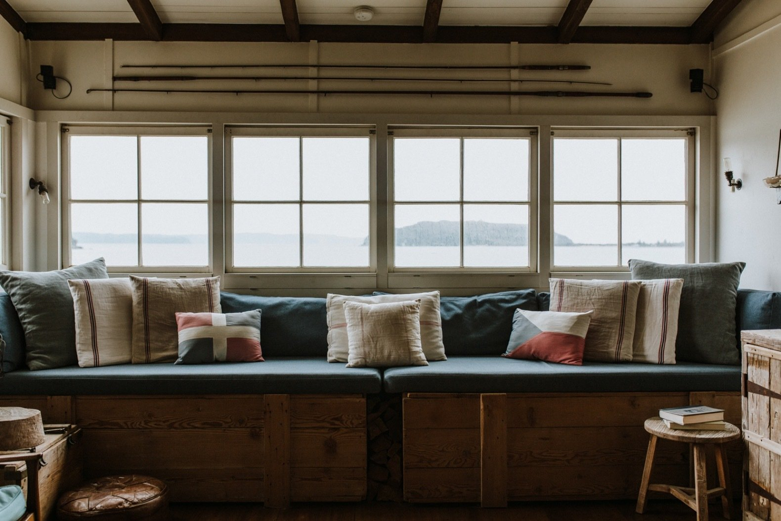 Living Room, Stools, Storage, Bench, Medium Hardwood Floor, and Wall Lighting A full-length window seat overlooks views of the beach and the bay.  Photo 8 of 11 in A 1920s Fisherman's Shack in Australia Breathes New Life as a Cozy, Unique Rental