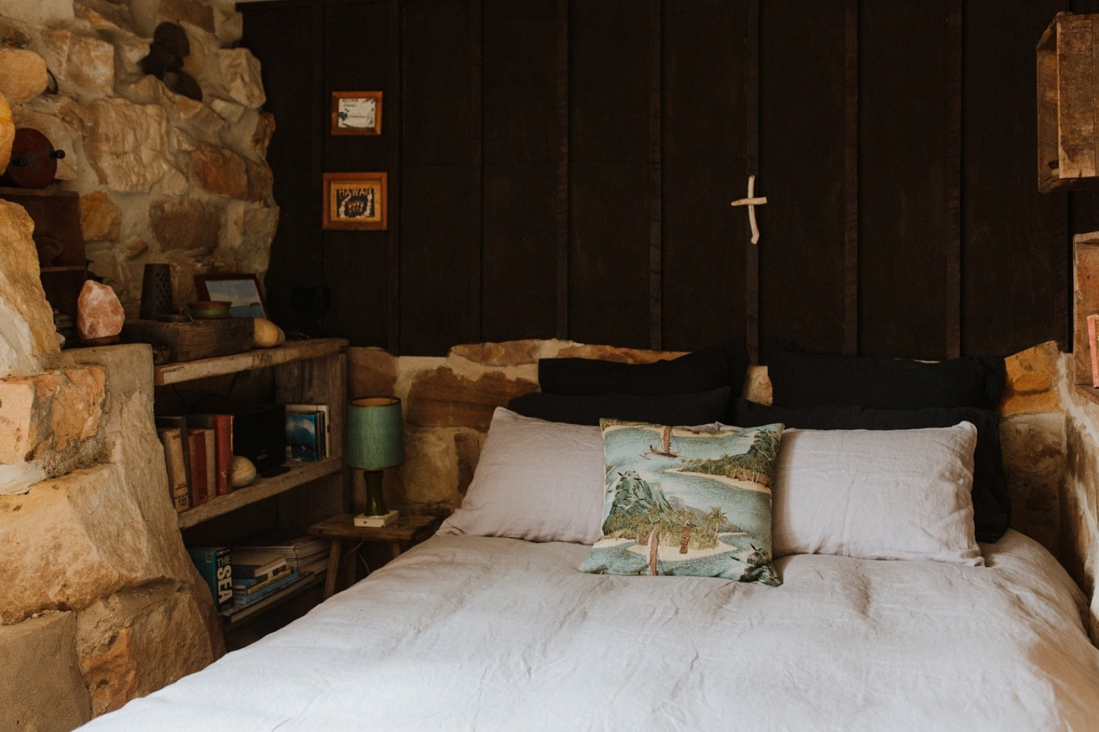 Bedroom, Shelves, and Bed The second bedroom, located on a lower level, includes a handmade queen bed nestled between walls that have been built from original sandstone and lined with timber.  Photo 11 of 11 in A 1920s Fisherman's Shack in Australia Breathes New Life as a Cozy, Unique Rental