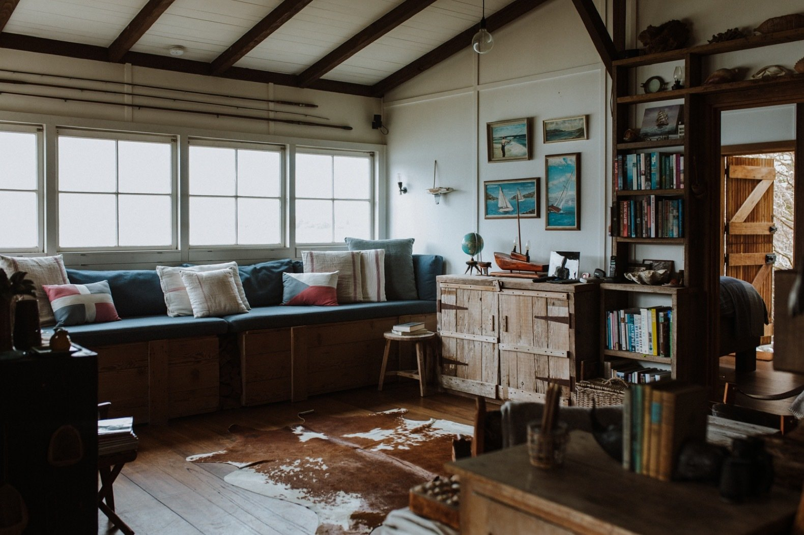 Living Room, Stools, Chair, Bookcase, Pendant Lighting, Medium Hardwood Floor, Shelves, Bench, and Rug Floor The couple built many furnishings, such as the storage chests, out of old leftover timber.  Photo 6 of 11 in A 1920s Fisherman's Shack in Australia Breathes New Life as a Cozy, Unique Rental