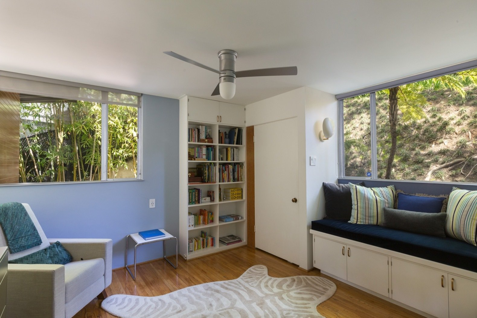 Bedroom, Chair, Storage, Ceiling Lighting, Medium Hardwood Floor, Bookcase, Rug Floor, Wall Lighting, and Bench Pale blue hues—repeated elsewhere in the home—stay true to Neutra's color palette.  Photo 10 of 15 in Calling All Richard Neutra Fans—His Bonnet House in L.A. Hits the Market at $1.8M