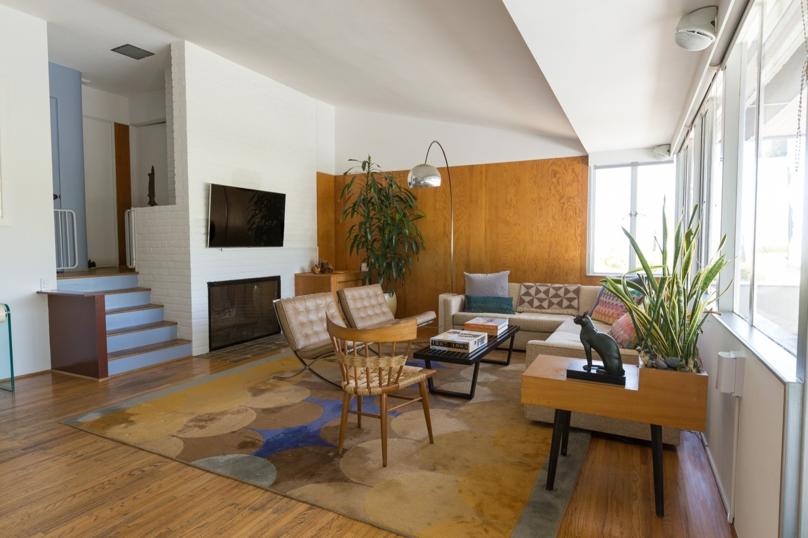Living Room, Coffee Tables, Floor Lighting, Medium Hardwood Floor, Chair, Sofa, Rug Floor, and End Tables Wood paneling adds a touch of warmth to the great room.   Photo 7 of 15 in Calling All Richard Neutra Fans—His Bonnet House in L.A. Hits the Market at $1.8M
