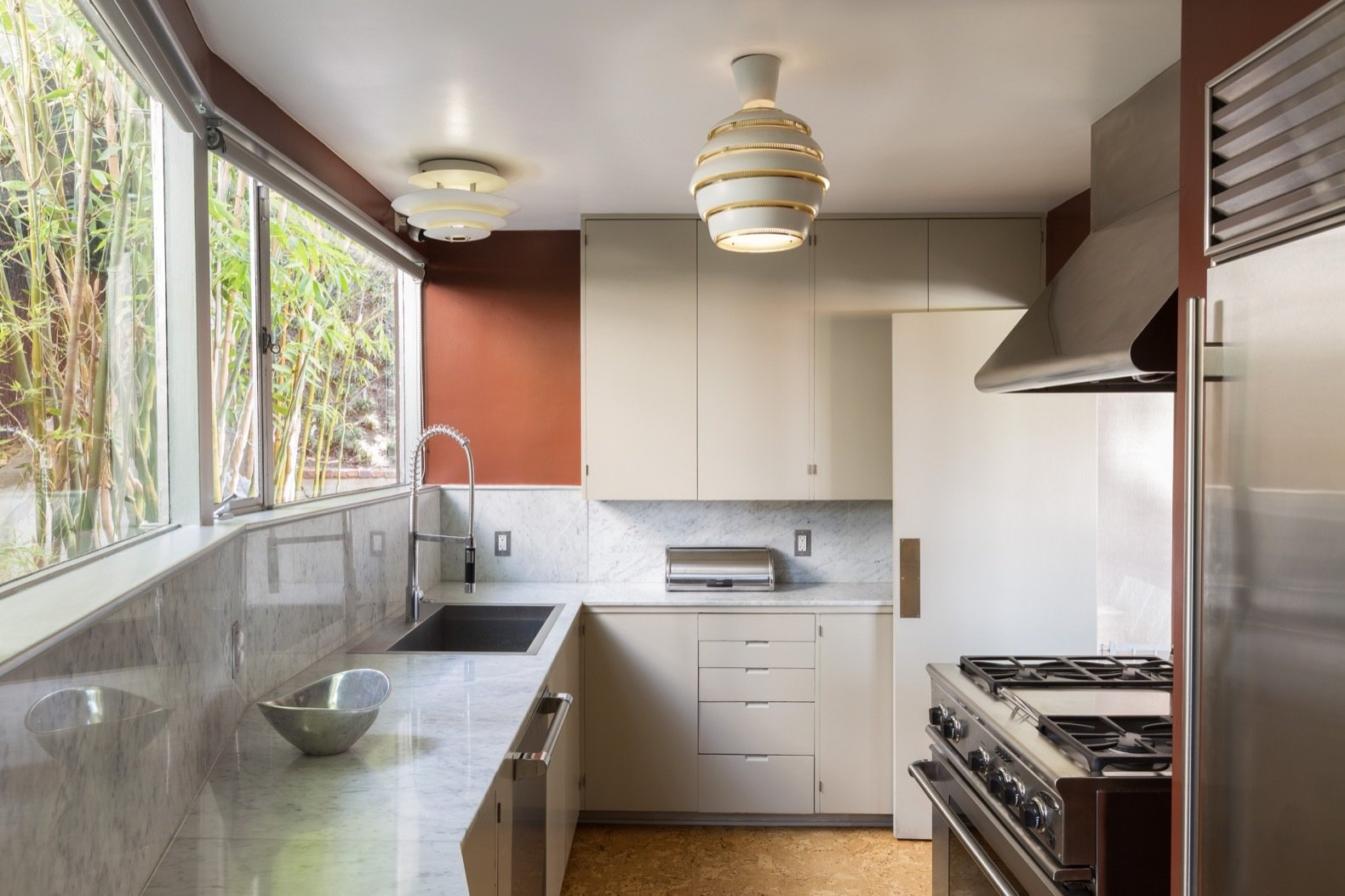 Kitchen, Ceiling Lighting, Laminate Counter, Cork Floor, Refrigerator, Range, Drop In Sink, and Range Hood The kitchen features cork flooring and an Alvar Aalto Beehive pendant lamp.  Photo 6 of 15 in Calling All Richard Neutra Fans—His Bonnet House in L.A. Hits the Market at $1.8M