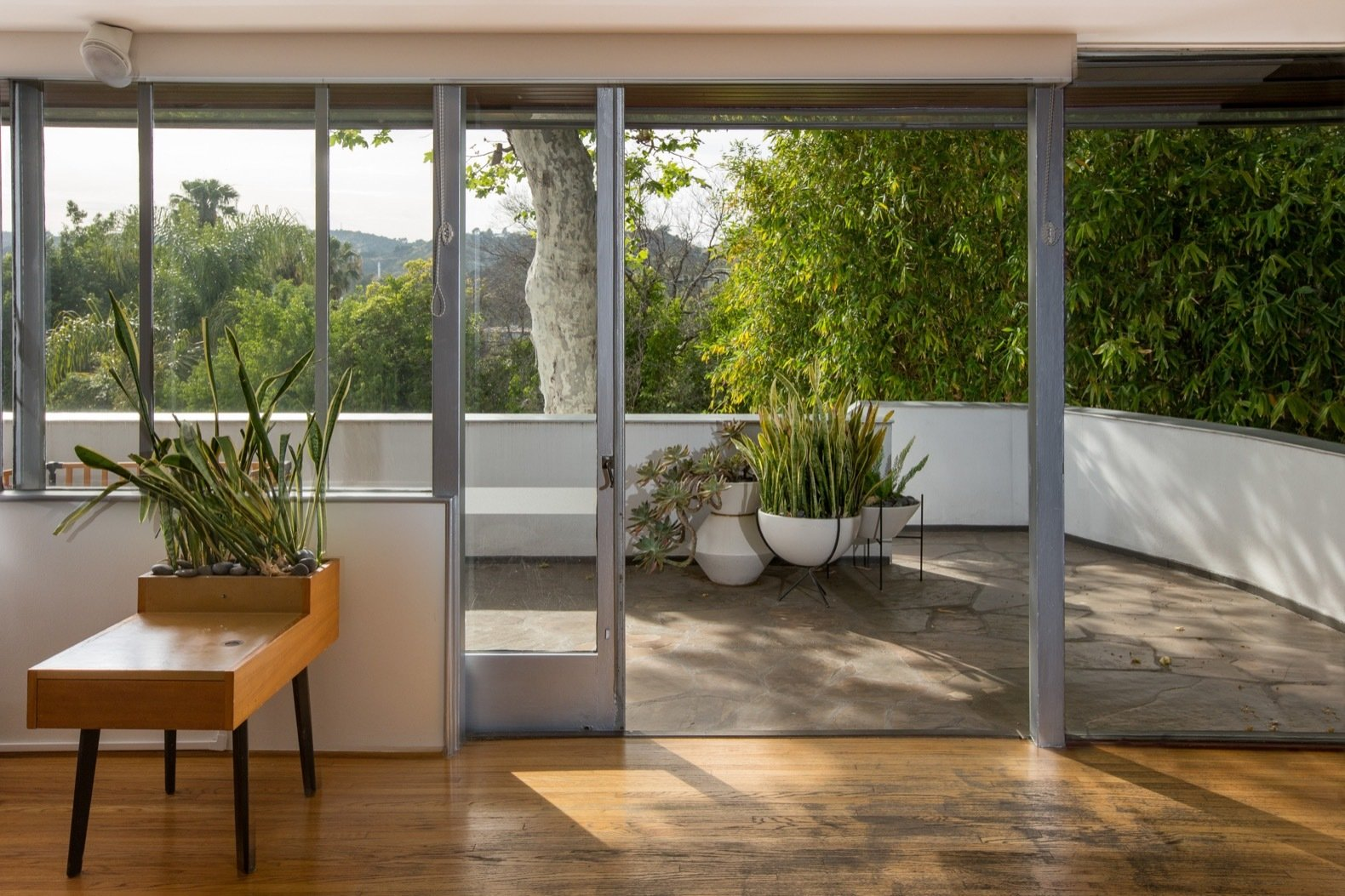 Living Room, Medium Hardwood Floor, and End Tables Sliding doors open the great room up to the outdoors.   Photo 14 of 15 in Calling All Richard Neutra Fans—His Bonnet House in L.A. Hits the Market at $1.8M