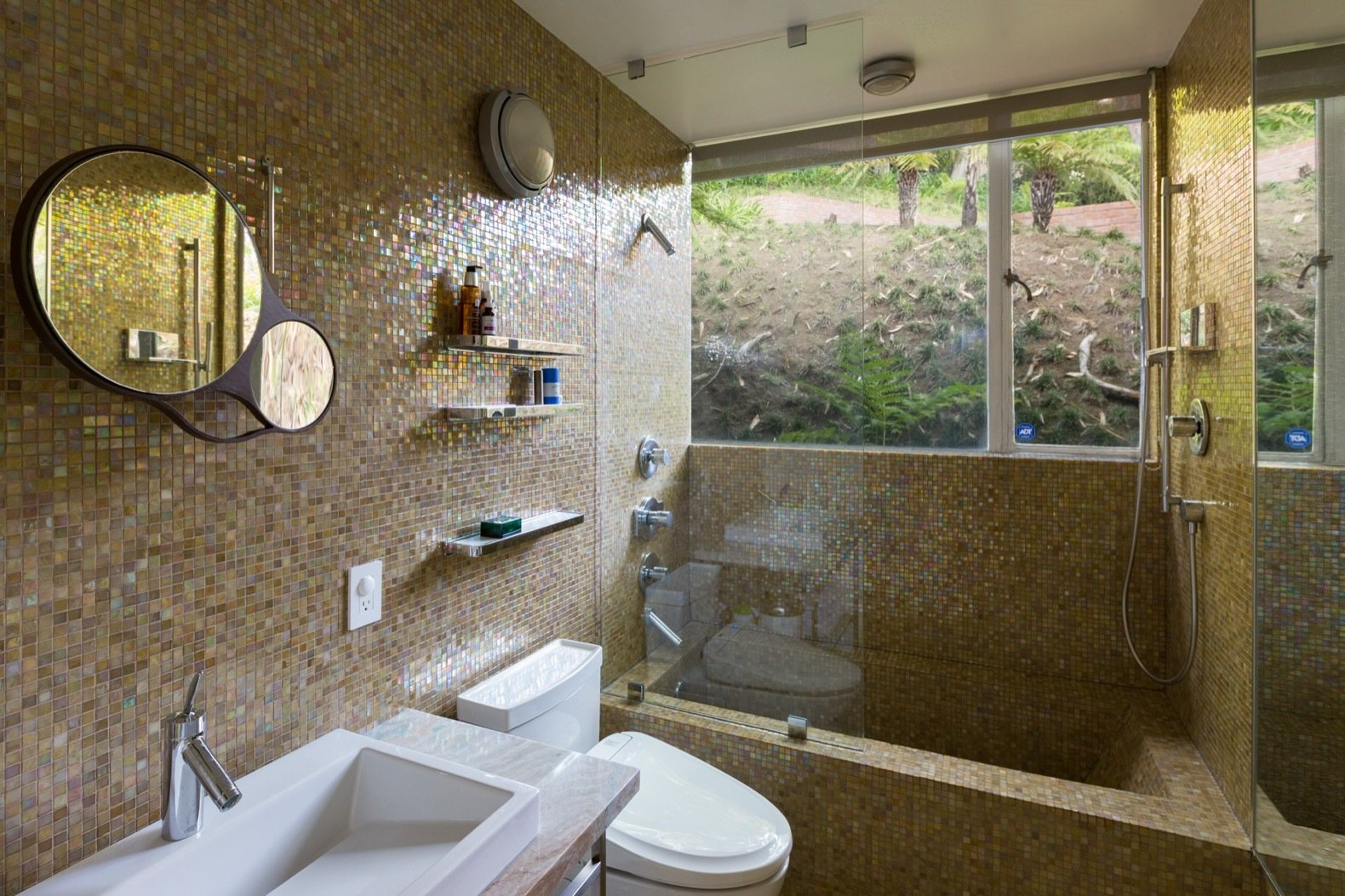 Bath Room, Wall Lighting, Ceiling Lighting, Drop In Sink, Soaking Tub, Mosaic Tile Wall, and Two Piece Toilet Colored tiles line the bathroom, which is set deep into the slope.    Photo 11 of 15 in Calling All Richard Neutra Fans—His Bonnet House in L.A. Hits the Market at $1.8M