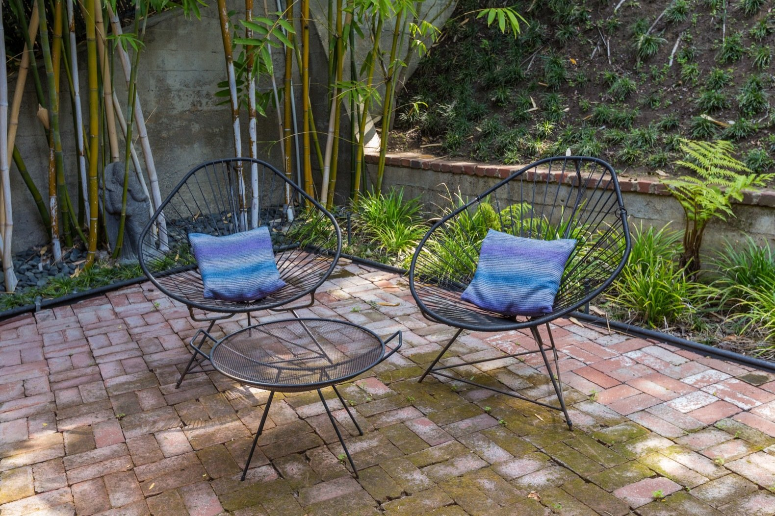 Outdoor, Small Patio, Porch, Deck, Grass, Pavers Patio, Porch, Deck, and Back Yard A bamboo grove provides privacy to the brick-paved patio in the backyard.    Photo 12 of 15 in Calling All Richard Neutra Fans—His Bonnet House in L.A. Hits the Market at $1.8M