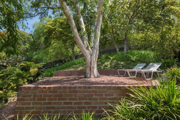 Tucked away from the street is a side yard that travels up behind the home to a flat viewing terrace, shaded beneath a large tree.