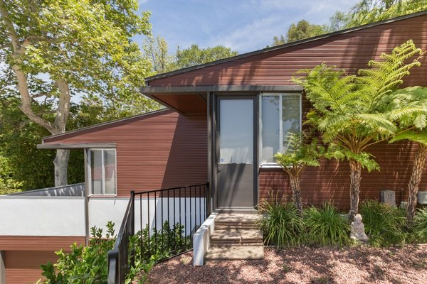 Previous owners had painted the redwood siding pink, so Hay—unable to strip the paint out of the wood—repainted the exterior a dark reddish-brown in an imitation of the siding's original color and texture.
