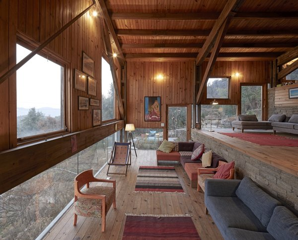 The living room overlooks the landscape through a low horizontal band of glass.