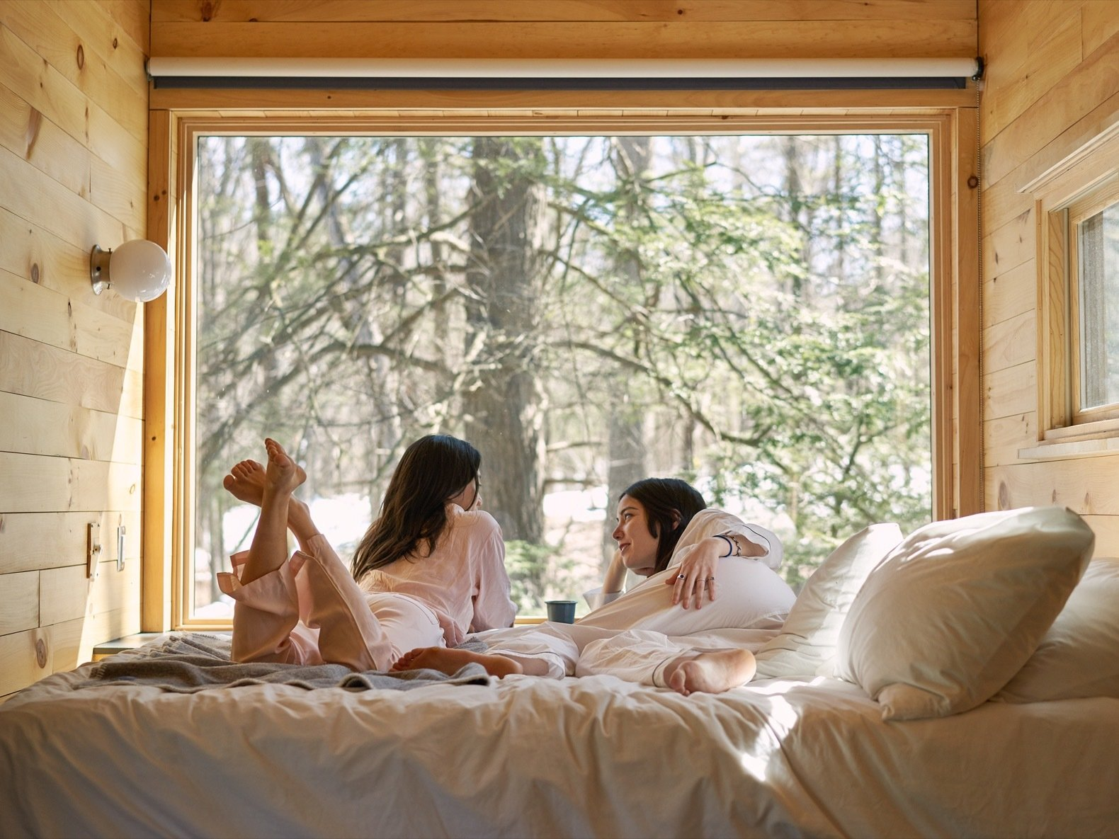Bedroom, Wall Lighting, Medium Hardwood Floor, and Bed As a digital detox destination, the cabins are WIFI-free and have little-to-no cell service.    Photo 1 of 9 in Rediscover the Pleasure of Solitude in These Micro Cabins Across the East Coast