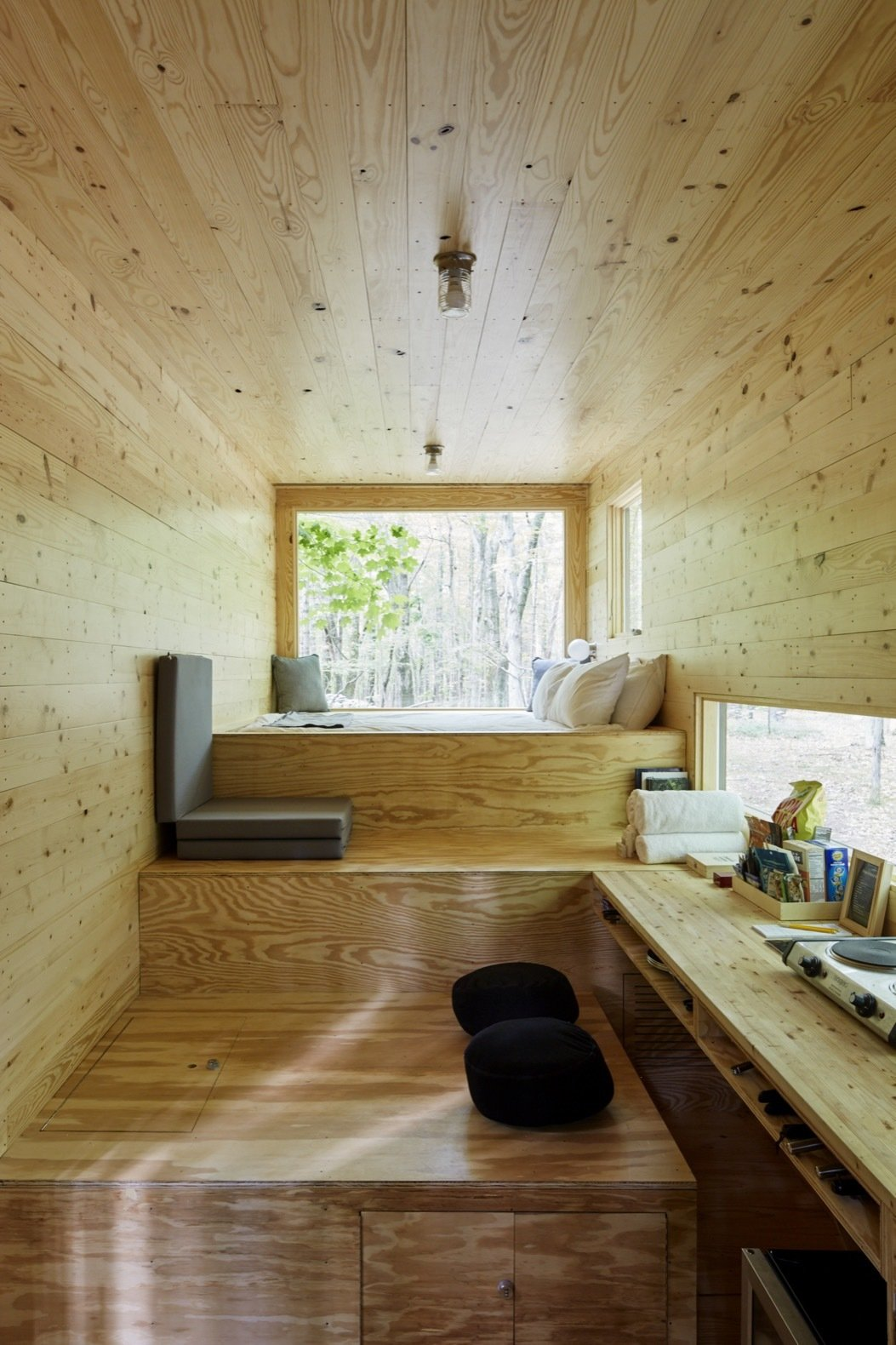 Living Room, Medium Hardwood Floor, Ceiling Lighting, and Bench The cabins—all designed in-house—sport a minimalist aesthetic, deliberately pared-down to let nature take the spotlight.     Photo 4 of 9 in Rediscover the Pleasure of Solitude in These Micro Cabins Across the East Coast
