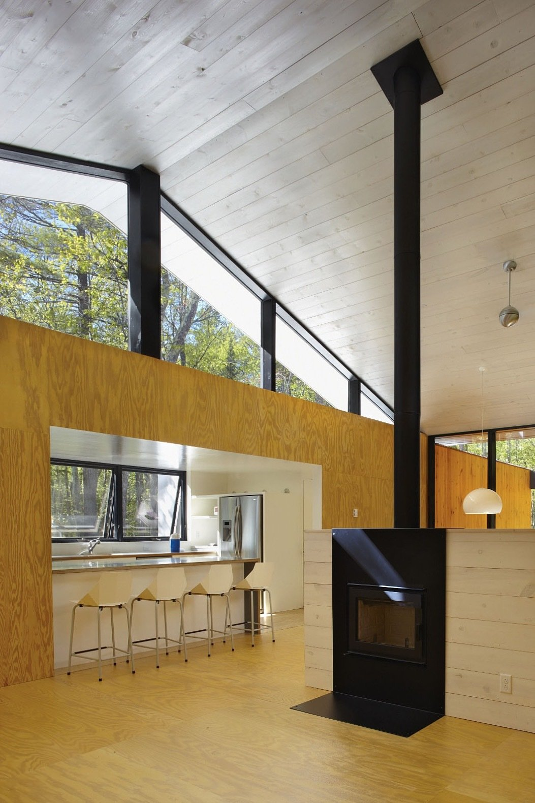 Windows and Metal Clerestory windows bring in additional light and views of the forest canopy.   Photo 13 of 15 in This Prefab Cabin Offers an Affordable Answer to Island Construction