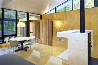 A screen of wooden posts marks the entrance and continues from the exterior to the interior.