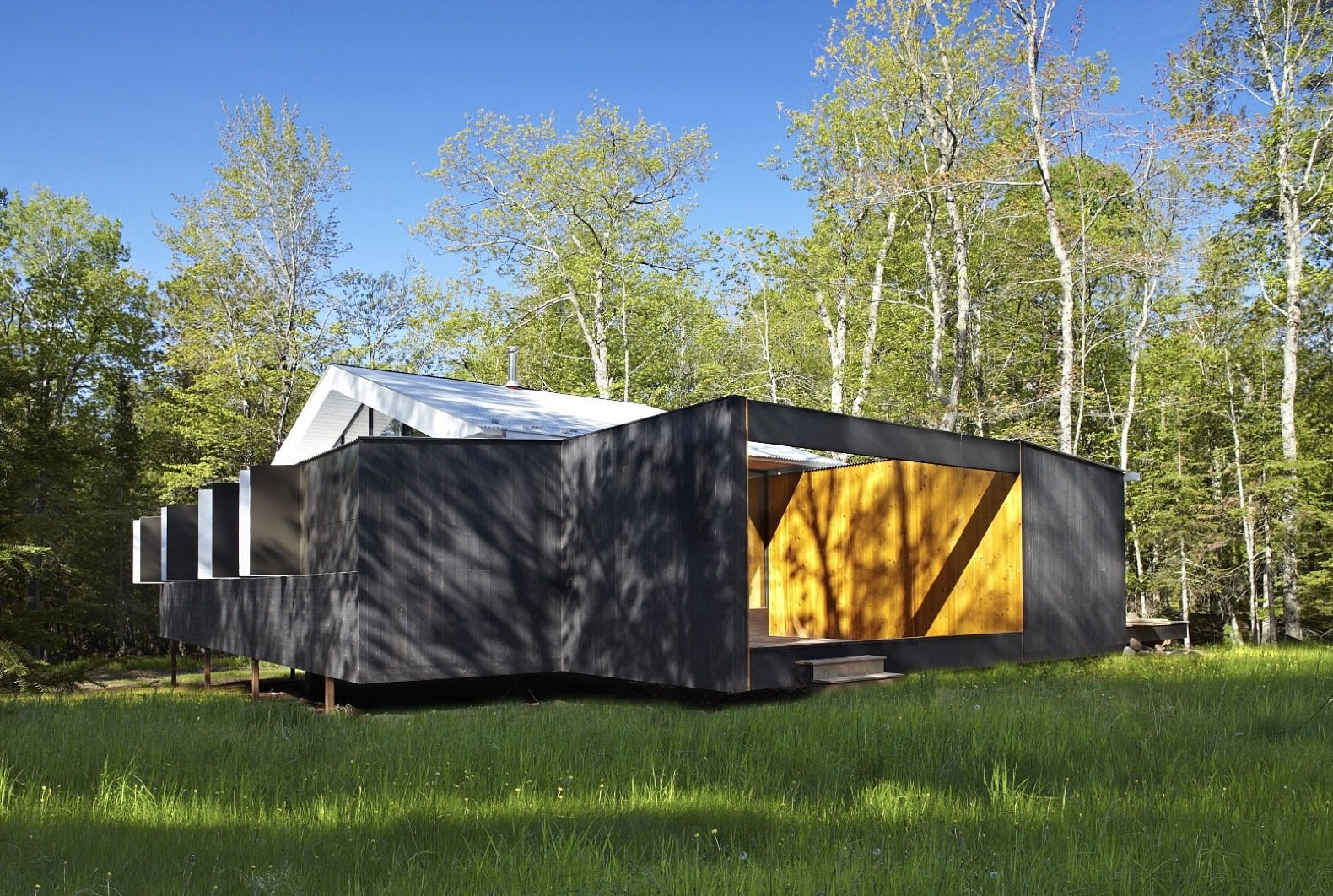 Exterior, Cabin Building Type, Prefab Building Type, Wood Siding Material, Gable RoofLine, and Metal Roof Material The exterior is coated in Sherwin Williams Solid Wood stain.   Photo 2 of 15 in This Prefab Cabin Offers an Affordable Answer to Island Construction