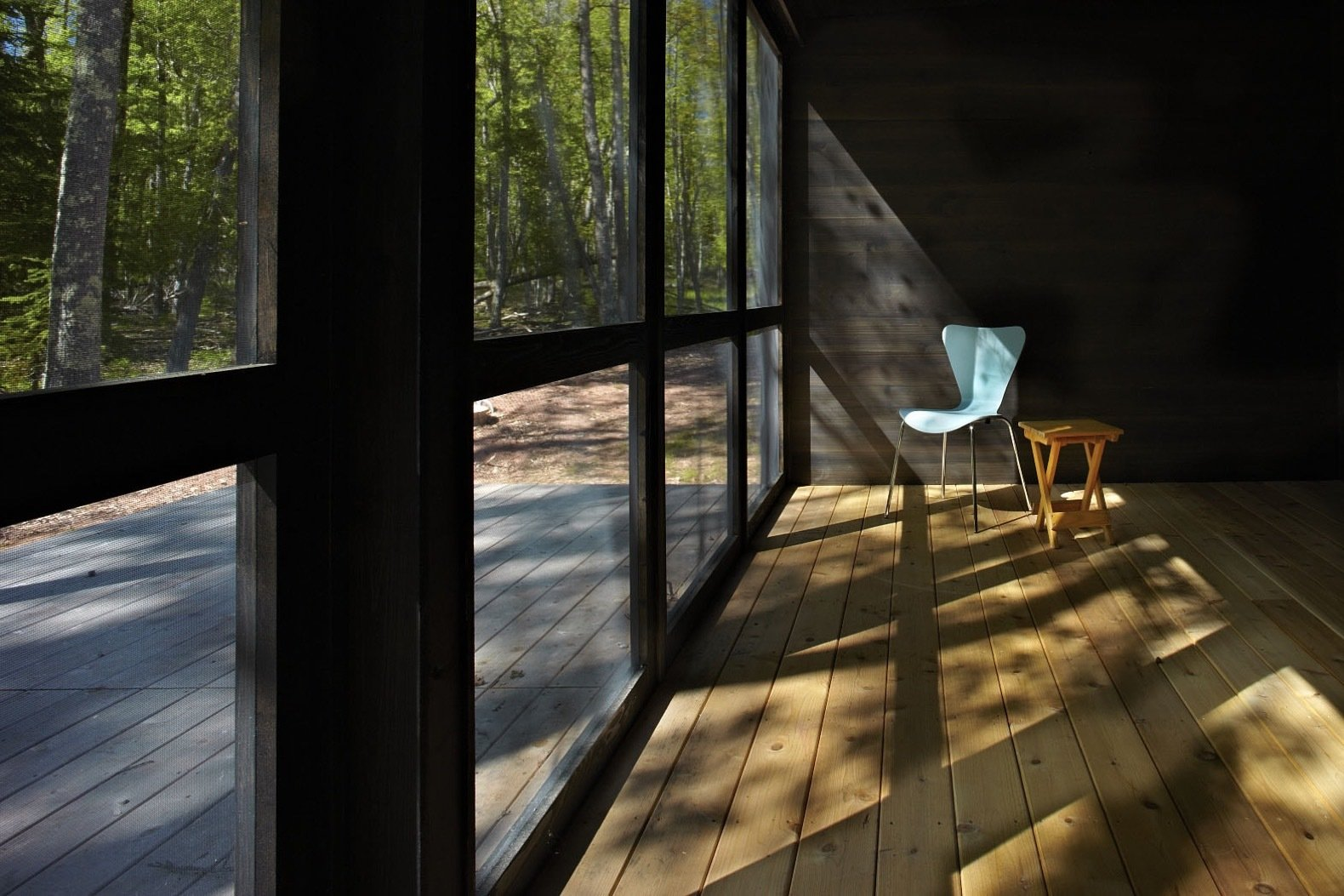 Living Room, Chair, Medium Hardwood Floor, and End Tables The screen porch frames views of the dense woods.    Photo 14 of 15 in This Prefab Cabin Offers an Affordable Answer to Island Construction