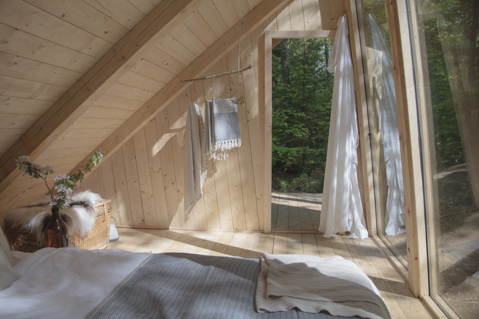 Bedroom, Light Hardwood Floor, and Bed The lodging interiors have been dressed in organic bed linen with large comfortable beds, beautiful handcrafted and recycled furnishings, and wood-fired stoves.    Photo 12 of 18 in This Swedish Permaculture Retreat Is a Foodie's Paradise