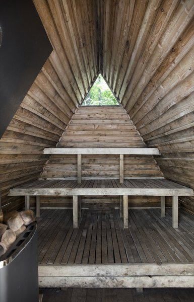 A small triangular window punctuates the interior of the floating sauna.