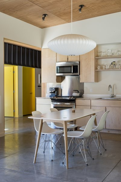 Plywood cabinetry and ceiling panels combine with white walls in a clean kitchen setting. A Modernica Nelson Bubble Lamp hangs above the dining table.