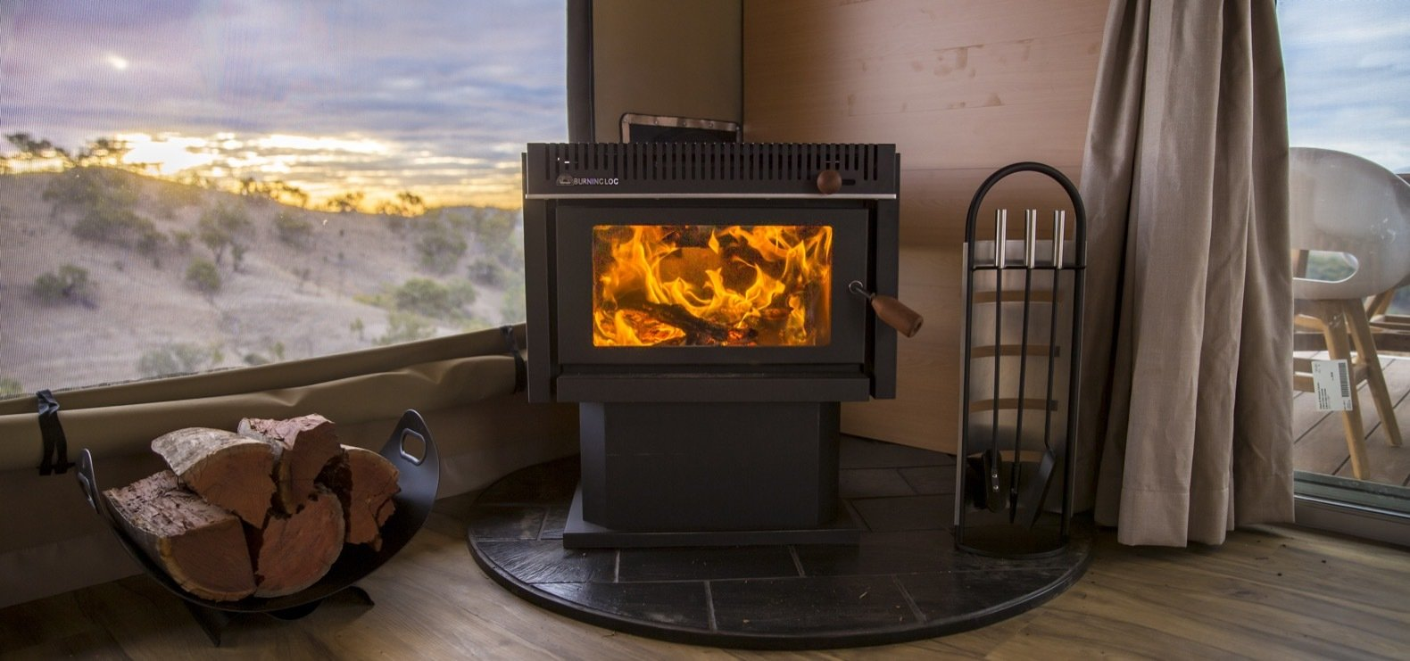 Living Room, Medium Hardwood Floor, and Wood Burning Fireplace In addition to a spacious bath, Dulili also features a designer kitchen, a wood-burning fireplace, screened windows, and a fire pit.  Photo 7 of 11 in Escape to the Australian Bush in Style With These Eco-Friendly, Luxe Tents