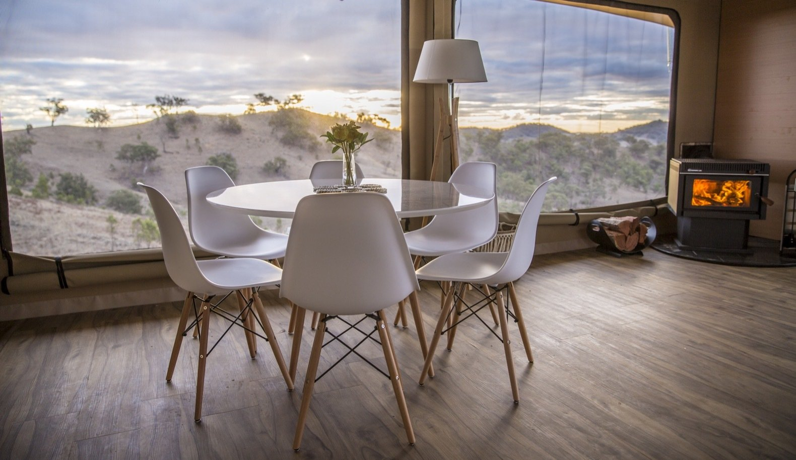 Dining Room, Table, Chair, Wood Burning Fireplace, Medium Hardwood Floor, and Floor Lighting Large fly windows and doors open the interiors up to the outdoors.  Photo 6 of 11 in Escape to the Australian Bush in Style With These Eco-Friendly, Luxe Tents