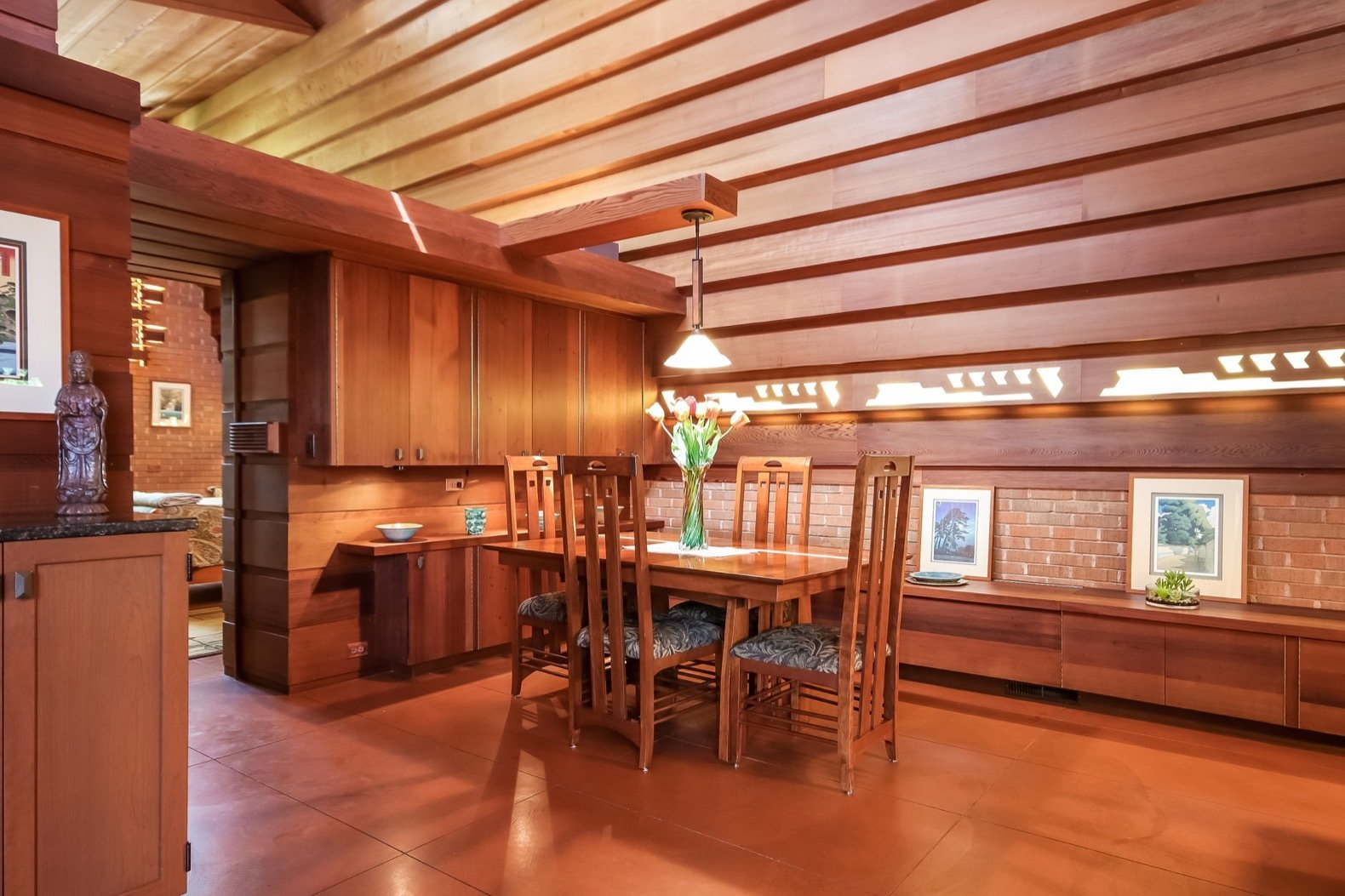 Dining Room, Chair, Table, Pendant Lighting, Storage, and Concrete Floor Reddish concrete floors can be found throughout. Wright's original gravity heating system still works.  Photo 6 of 17 in A Gorgeous Frank Lloyd Wright Home Hits the Market For the First Time at $1.2M