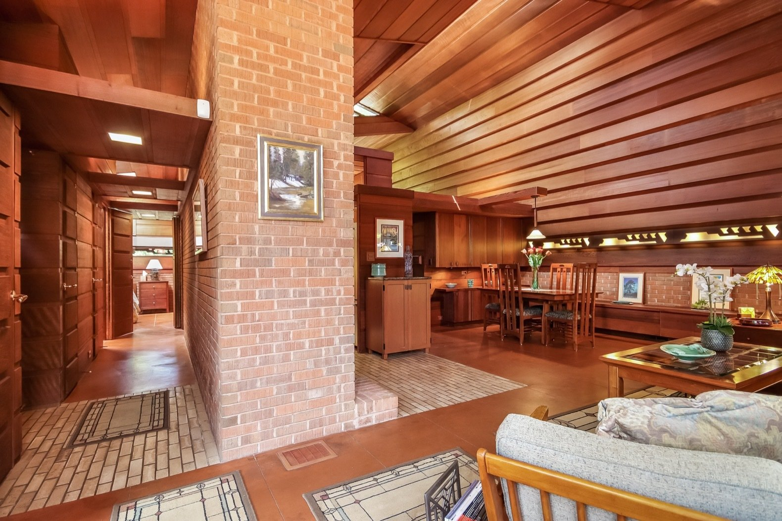 Hallway, Brick Floor, and Concrete Floor The foyer, marked by brick paving, leads to a hallway to the left and the great room to the right.  Photo 4 of 17 in A Gorgeous Frank Lloyd Wright Home Hits the Market For the First Time at $1.2M
