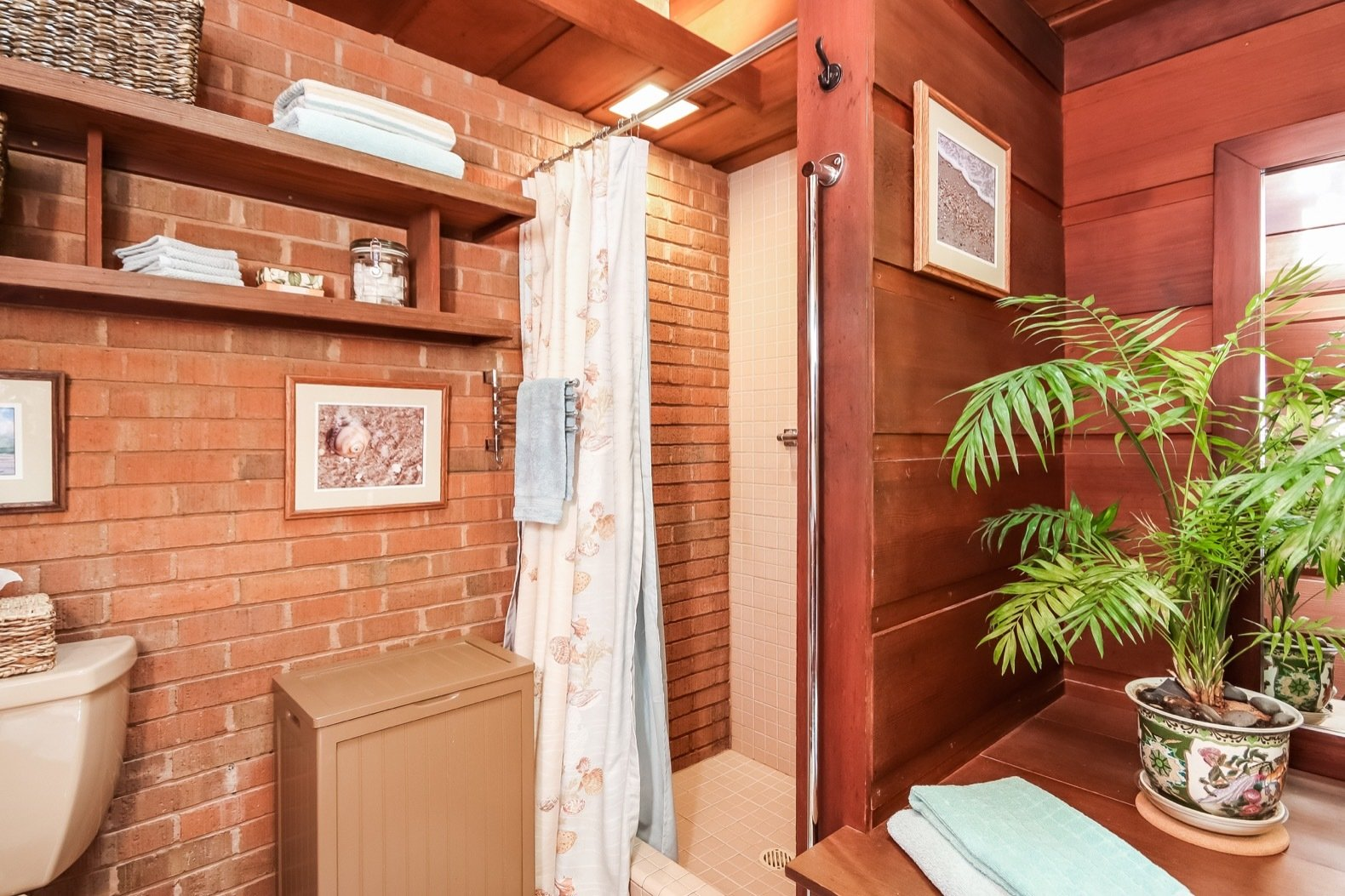 Bath Room, Wood Counter, Concrete Floor, Two Piece Toilet, Corner Shower, and Ceiling Lighting The master bathroom boasts an exposed brick wall.  Photo 11 of 17 in A Gorgeous Frank Lloyd Wright Home Hits the Market For the First Time at $1.2M