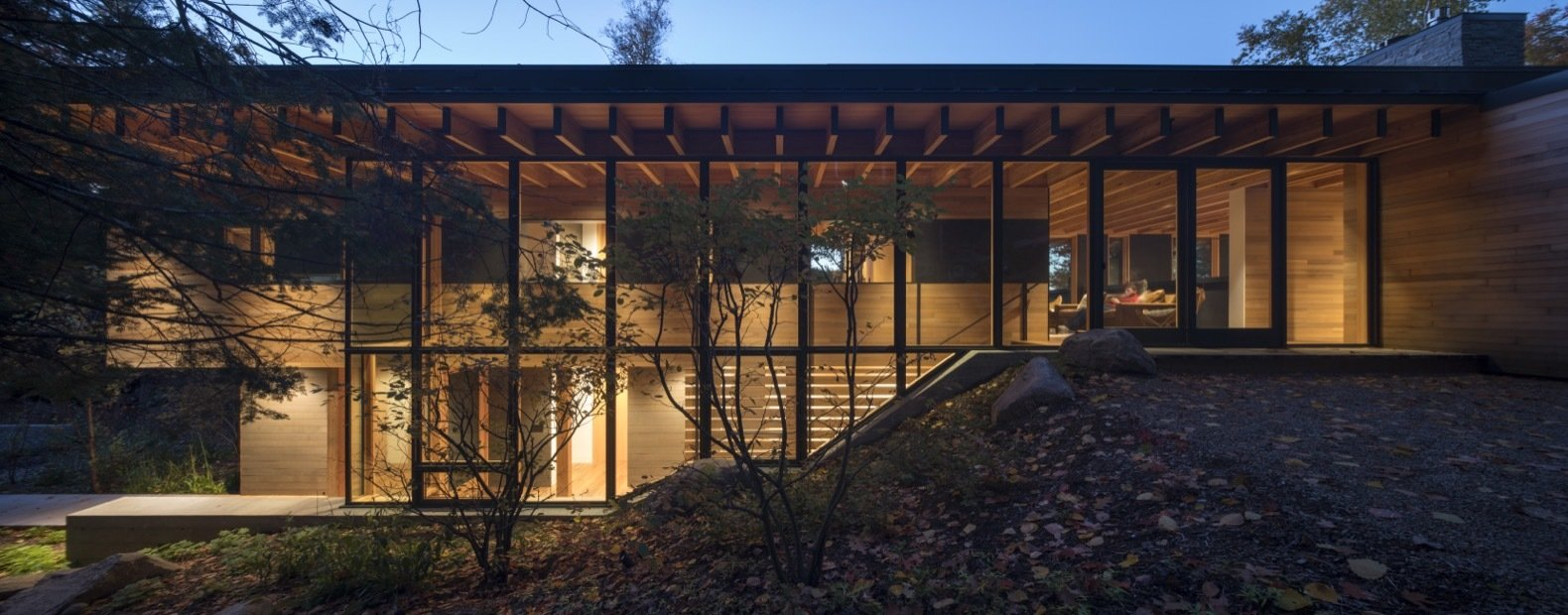 Exterior, House Building Type, Metal Roof Material, Concrete Siding Material, Wood Siding Material, Glass Siding Material, Flat RoofLine, and Cabin Building Type A glazed staircase placed on the south side of the building next to the hillside leads to the bedrooms on the upper level.    Photo 4 of 16 in This Award-Winning Cabin Is a Relaxing Antidote to City Living