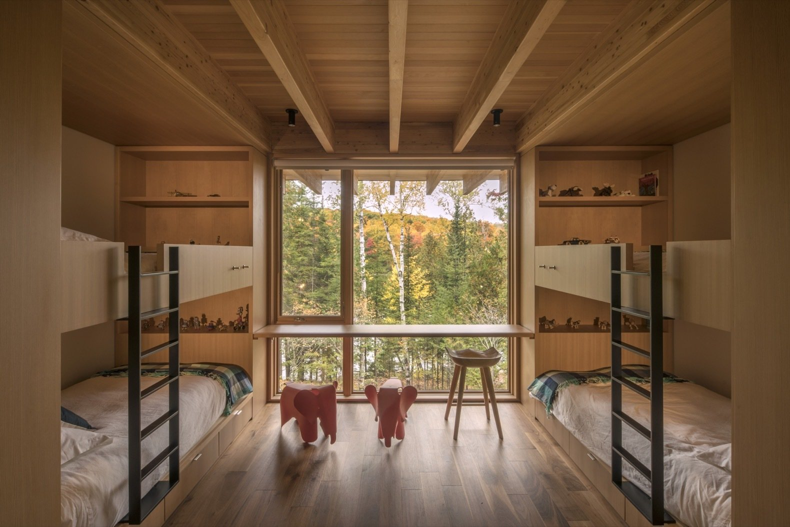 Kids, Chair, Bunks, Shelves, Bedroom, Desk, Neutral, and Medium Hardwood Oversized sliding doors open to the bunk room with floor-to-ceiling windows overlooking the serene lake.    Kids Bedroom Neutral Shelves Photos from This Award-Winning Cabin Is a Relaxing Antidote to City Living