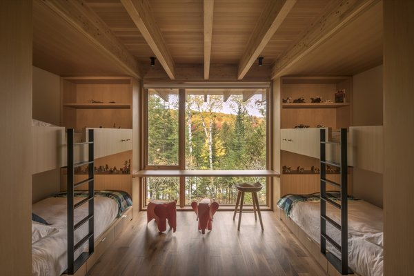 Oversized sliding doors open to the bunk room with floor-to-ceiling windows overlooking the serene lake.