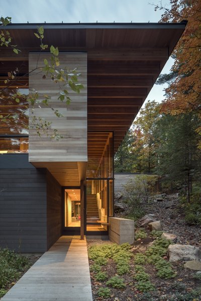 The rich material palette of stone, timber, glass, and board-formed concrete blend the home into the surroundings.