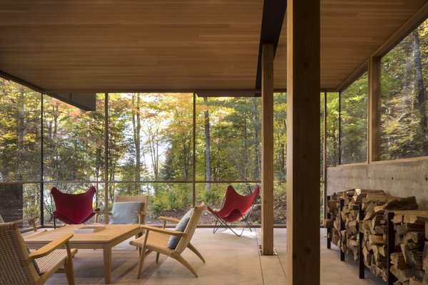Positioned for stellar outdoor views, the screened porch features concrete floors, a cedar ceiling, natural fir posts, and midcentury chairs.