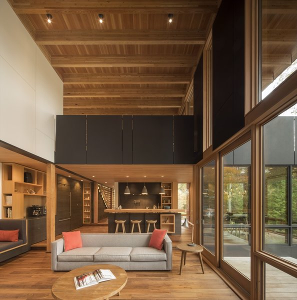The den, located above the living room, connects to an at-grade fire pit terrace to the south, as well as an elevated deck with views of the lake to the north.