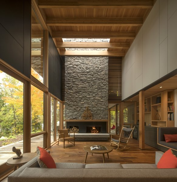 The great room is anchored by a 25-foot-high granite, wood-burning fireplace with a reclaimed timber mantle located beneath Alumicor skylights.