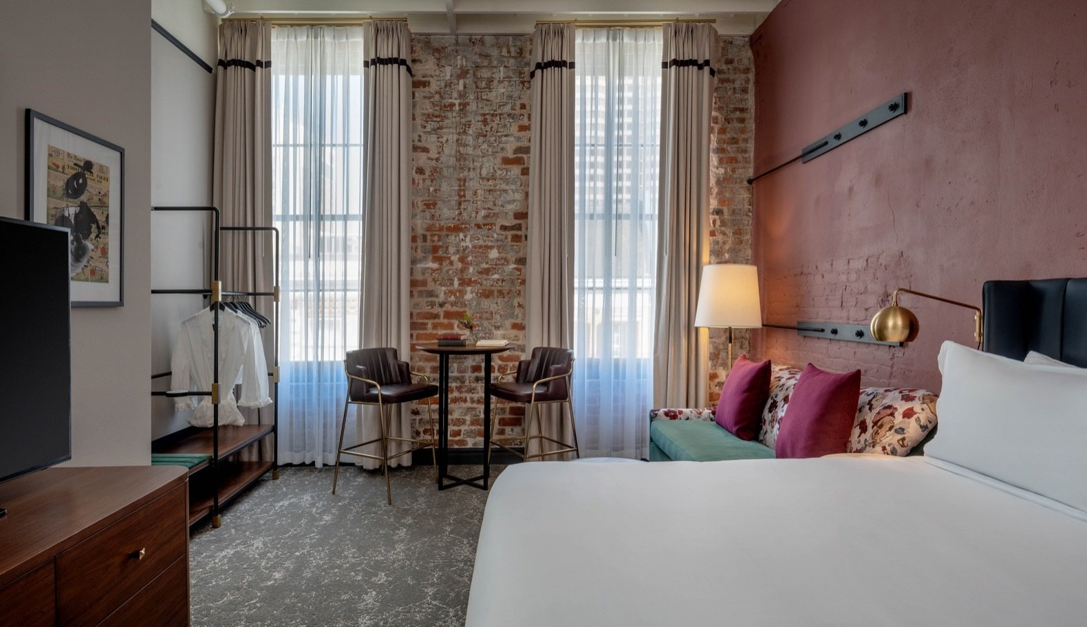 Bedroom, Carpet, Night Stands, Bed, Lamps, Chair, Floor, and Wall Exposed brick walls can be seen in the Premium King Suite, which overlooks views of Magazine Street.   Bedroom Carpet Floor Night Stands Photos from Seven Historic Warehouses Are Now a Sumptuous New Orleans Hotel