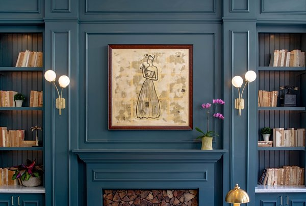 A closer look at the front desk with painted paneled walls, built-in bookshelves. a decorative fireplace, and a framed sketch of a figure evocative of Eliza Jane.
